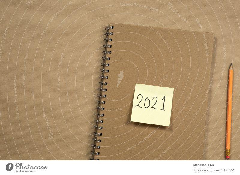 Draufsicht auf Brown Notizblock und gelbe Haftnotiz mit 2021 Neujahrsbotschaft, Bleistift auf braunem Papier Hintergrund Textur, Bildung oder Business-Konzept