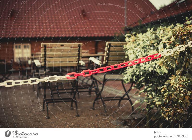 Mit einer rot-weißen Kette abgesperrter und geschlossener Außenbereich eines Restaurants in der Corona-Pandemie im Lockdown | corona thoughts Absperrung