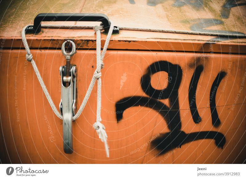 Mit einem Seil zugeknoteter orangefarbiger Müllcontainer | beschmiert mit schwarzer Farbe | Graffiti Mülltonne Müllbehälter Recycling Müllentsorgung