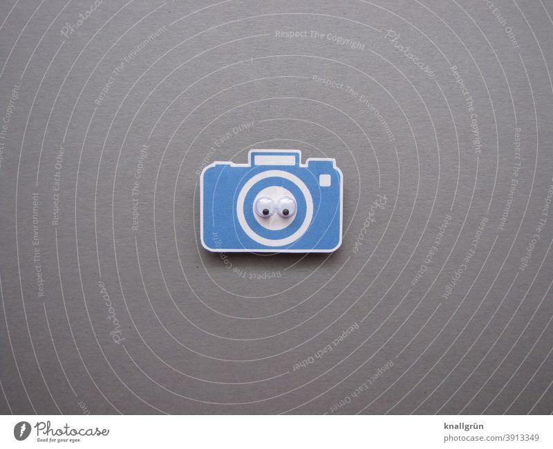 Kleine blaue Kamera aus Papier mit zwei Wackelaugen Blick Auge Blick in die Kamera ausgeschnitten Farbfoto weiß grau schwarz Zentralperspektive Nahaufnahme