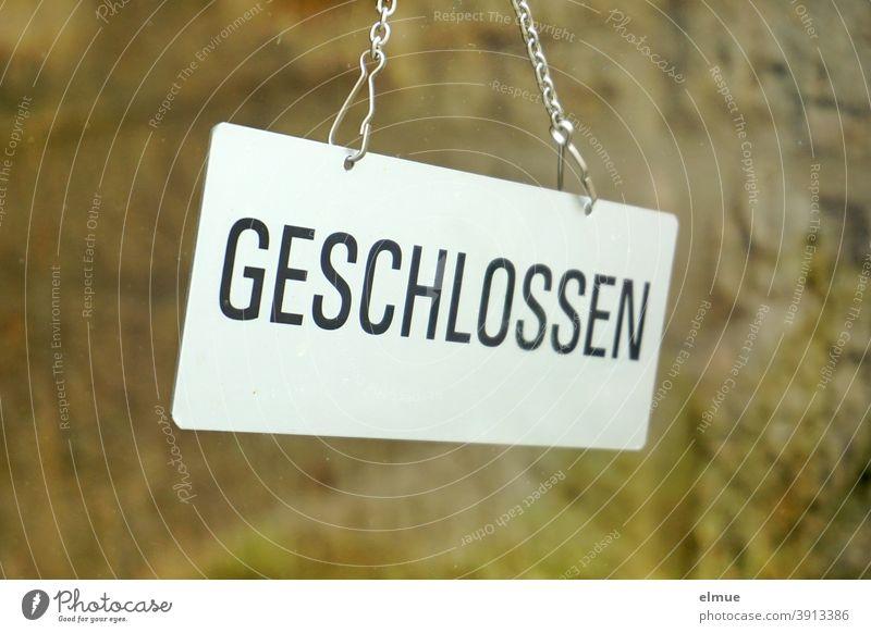 """Hinter einer Glasscheibe hängt ein Schild """"GESCHLOSSEN""""  / lockdown / Coronakrise geschlossen hängen Glastür Tür Hinweisschild Laden Geschäft Prävention"""