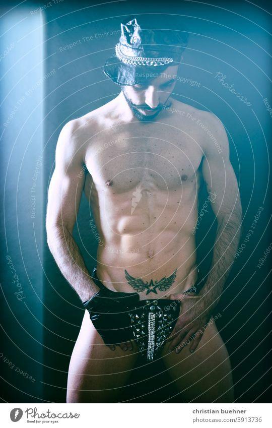 erotisches foto eines mannes nackt kappe nakter oberkoerper gay tatoo schnauzer bart unterhose string string tanga perlen glitzer model sex sexy sexy string