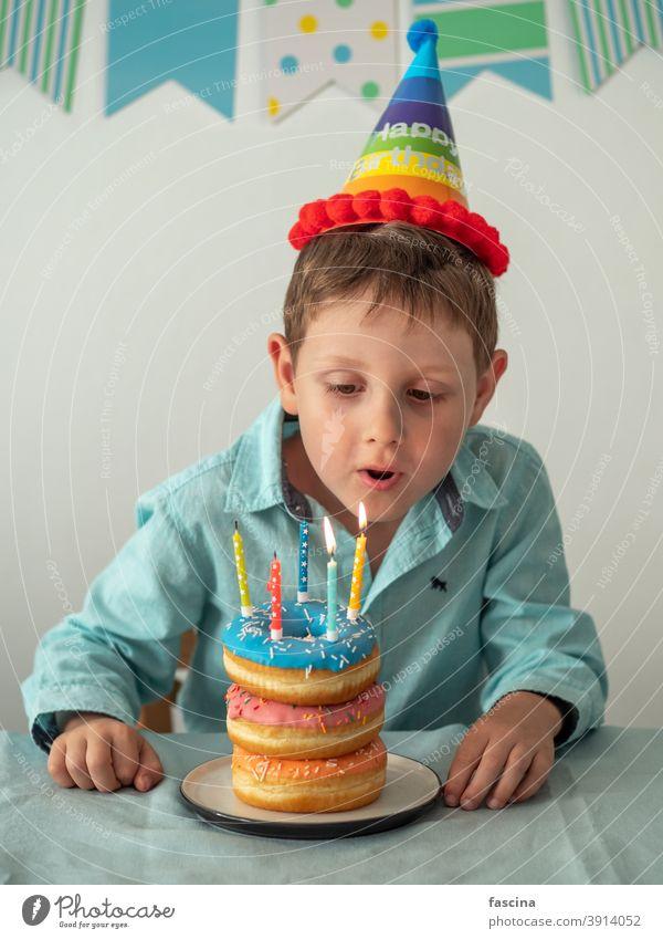 Kind bläst die Kerze auf Geburtstag Donuts Kuchen aus Schlag Krapfen Junge Hände fünf Jahr sein wenig Halt Teller Doughnut Spaß fünf Jahre alt Geburtstags-Donut