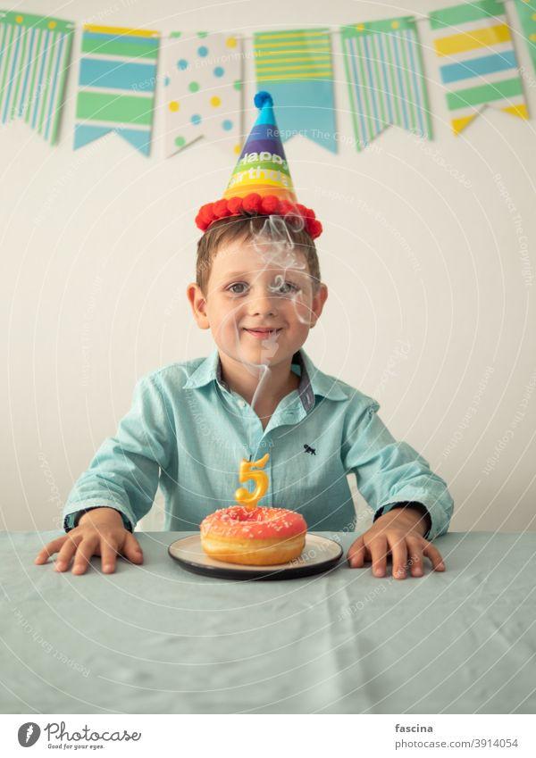 Kind durch Rauch von Kerze auf festlichen Donut Geburtstag Krapfen Junge Hände fünf Jahr sein wenig Lächeln Halt Teller Doughnut in die Kamera schauen Spaß