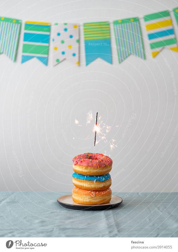 Geburtstag Donuts Kuchen mit Wunderkerze auf dem Tisch Donuts-Kuchen Bengallicht Girlande Geburtstags-Donuts Stapel süß Bengalen Licht lecker Doughnuts Party