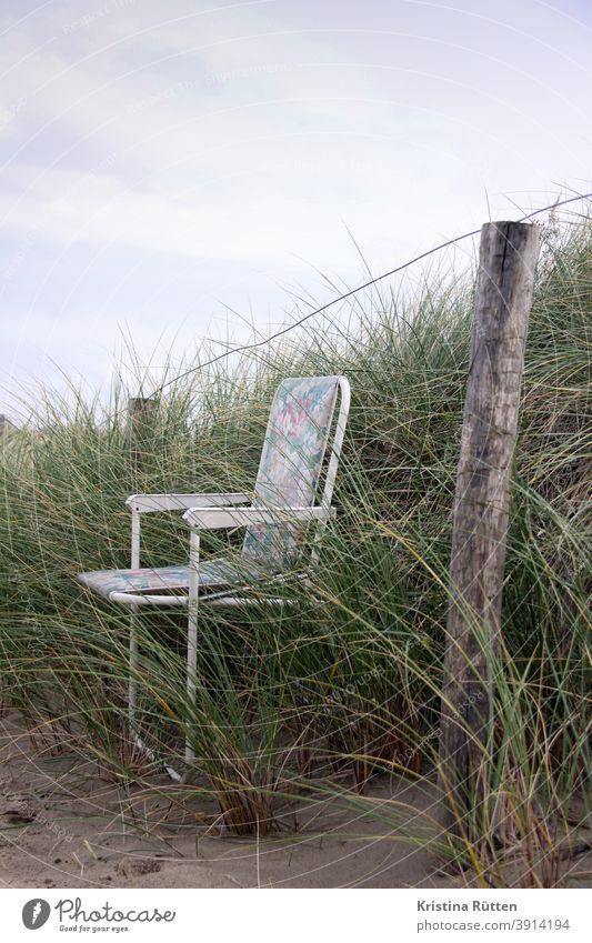 klappstuhl im dünengras campingstuhl gartenstuhl zaun abgestellt vergessen verlassen draußen sand natur leer einsam alleine auszeit pause sitzen ausruhen