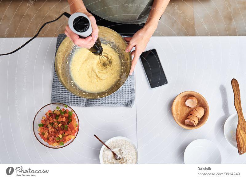 Frau in der Küche beim Backen eines Kuchens. Hände schlagen den Teig mit einem elektrischen Mixer, Ansicht von oben Essen zubereiten Koch Rezept Zutaten