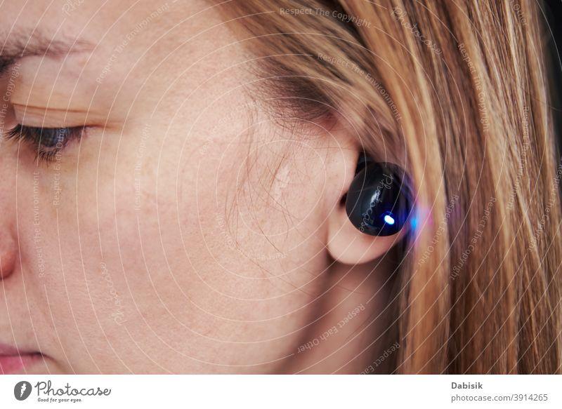 Frau hört Musik durch drahtlose Kopfhörer. Kaukasische Frau mit bluetooth Kopfhörer im Ohr, Nahaufnahme Drahtlos Audio zuhören Bluetooth schwarz Gerät digital