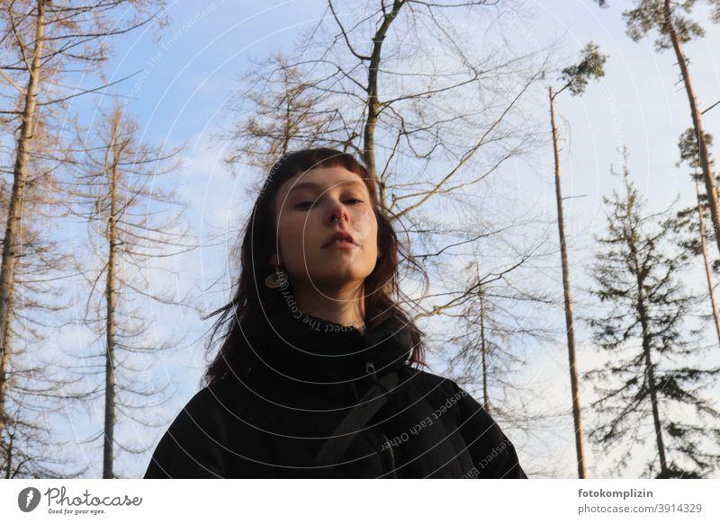 Porträt  einer jungen herabschauenden Frau unter kahlen Bäumenwipfeln Frauengesicht Portrait portrait Identität Gesicht langhaarig weiblich Selbstbewusstsein