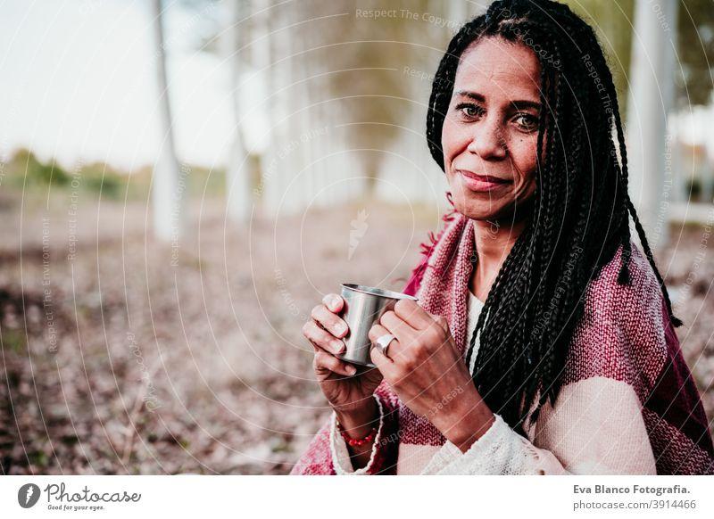 Porträt der hispanischen Mitte erwachsene Frau im Freien halten in Decke gewickelt. Halten Becher Wasser Wasser während picnic.Autumn Saison Herbst Afrofrau