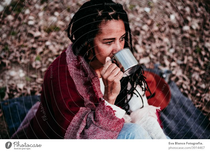 Porträt von hispanischen Mitte erwachsene Frau im Freien halten in Decke eingewickelt. Trinkwasser während picnic.Autumn Saison Herbst Afrofrau Latein