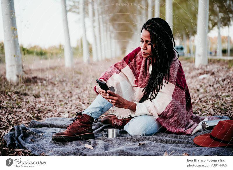 Porträt von hispanischen Mitte erwachsene Frau im Freien halten in Decke eingewickelt. Mit Handy während Picknick.Herbstsaison Afrofrau Latein Sonnenuntergang