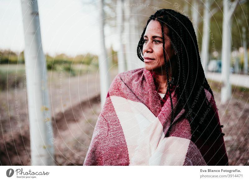 Porträt von hispanischen Mitte erwachsene Frau im Freien halten in Decke eingewickelt. Herbstzeit Afrofrau Latein Sonnenuntergang Natur Hut Lächeln Glück