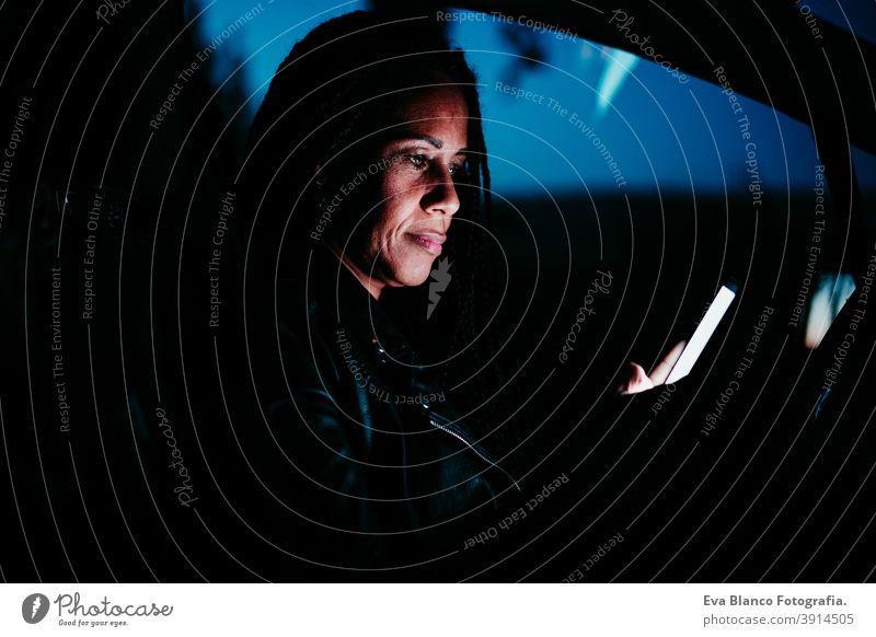 hispanische Frau mit Mobiltelefon im Auto bei Nacht. Reisen und Technologie Konzept Handy PKW Bildschirm reisen schön mittlerer Erwachsener Lebensstile klug
