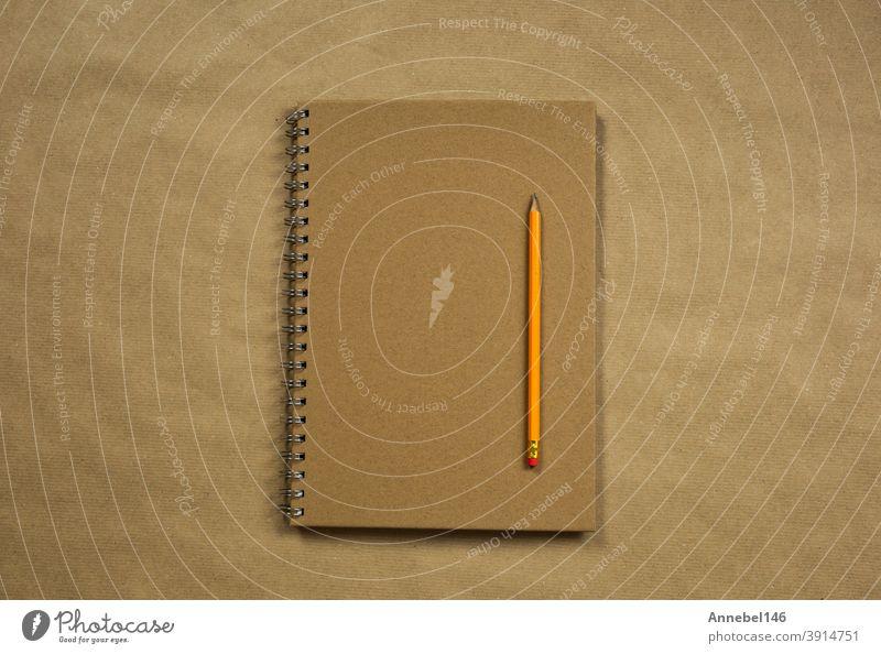 Braunes Notizbuch und klassischer Bleistift auf braunem Normalpapier Hintergrund Textur, Kopie Raum oder Raum für Text, Business oder Bildung Konzept Draufsicht modernen Retro-Design