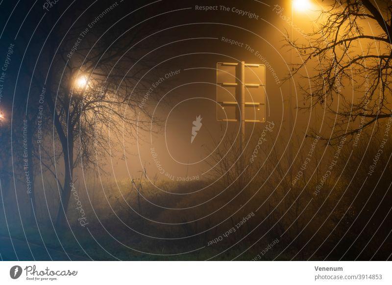 Nebel in den Straßen der Stadt Luckenwalde ,Verkehrsschild von hinten, Straßenlampe hinter einem Baum neblig Nacht Lichtmast Peitschenlaterne Straßenleuchte