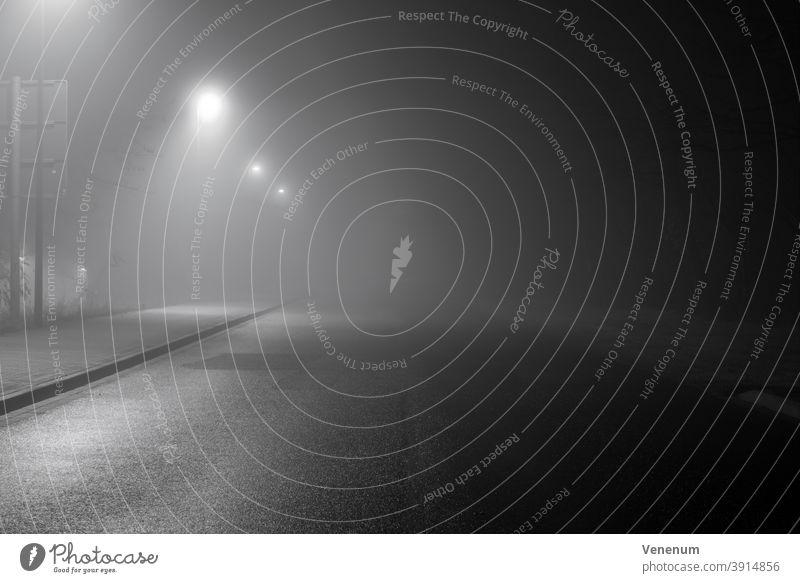 Nebel in den Straßen der Stadt Luckenwalde ,bei Nacht ohne Menschen neblig Lichtmast Peitschenlaterne Straßenleuchte beleuchtete Straßenlaterne Haus Häuser