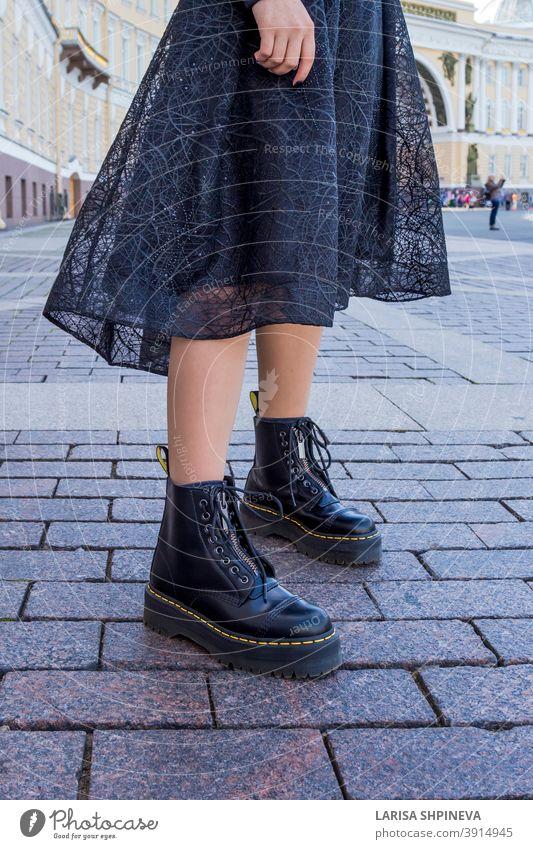 Ein Element der Garderobe einer modischen Frau ist ein schickes schwarzes Kleid und Stiefel. Mädchen Dame im Freien Porträt attraktiv Straße schön jung urban