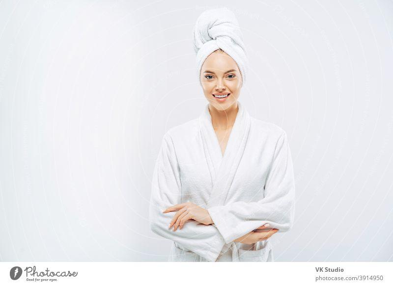 Schöne lächelnde junge Frau hat weiche gesunde Haut nach dem Duschen, trägt Bademantel und Handtuch auf den Kopf gewickelt, genießt Freizeit zu Hause, isoliert über weißem Hintergrund. Wellness-Konzept.