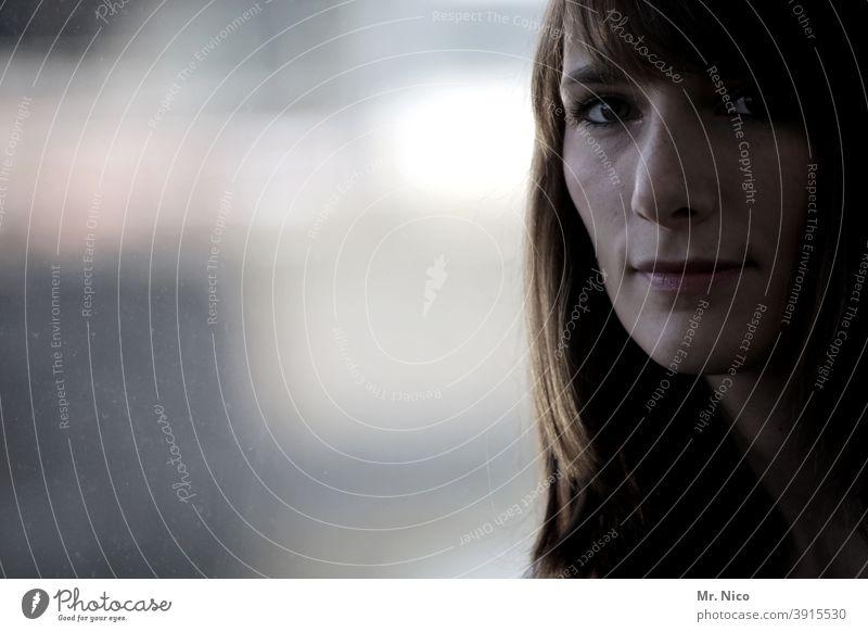 Frauengesicht im Halbschatten Fenster Kopf beobachten langhaarig schön nachdenklich verträumt Fensterscheibe Traurigkeit Reflexion & Spiegelung Gesicht