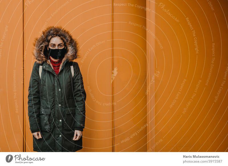 Frau mit Gesichtsmaske steht gegen orange Stadtmauer Erwachsener attraktiv schön Schönheit blond Busbahnhof Kaukasier Großstadt selbstbewusst Coronavirus