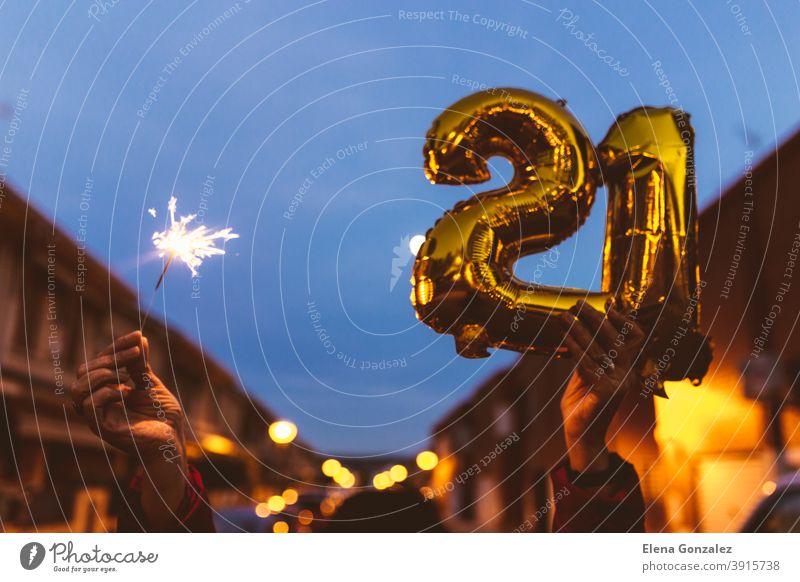 Feiern mit Goldfolie Ballons Ziffer 21 und Wunderkerze in der Nacht. Frohes neues Jahr 2021 Feier. zählen Jahre Funkelt Glückwünsche glänzend funkeln Konzepte