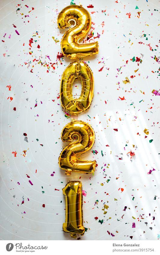 Goldfolie Ballons Ziffer 2021 mit bunten Konfetti auf weißem Hintergrund. Frohes neues Jahr 2021 Feier. zählen Jahre Einladung Glückwünsche glänzend funkeln