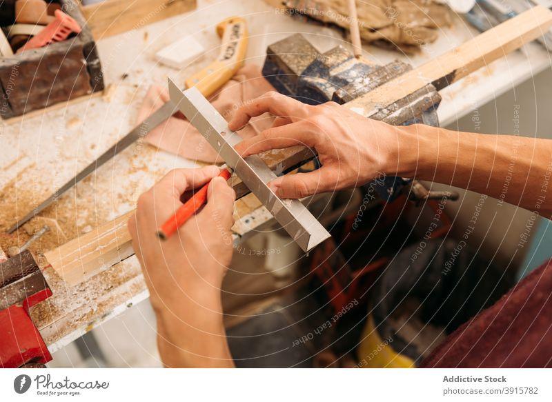 Crop Holzarbeiter mit Metallwinkel in der Werkstatt Tischlerin Zimmerer Winkel Mann Holzarbeiten Schreinerei Schiffsplanken männlich Spielfigur Kunsthandwerker