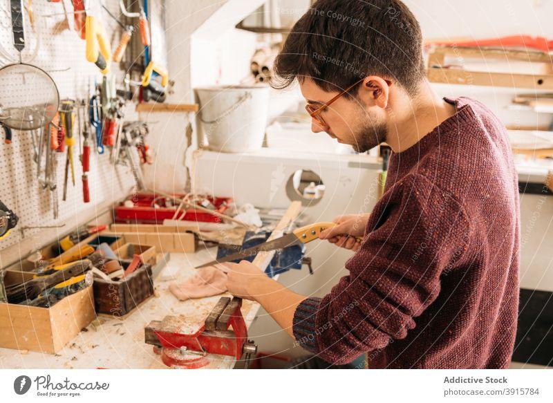 Fokussierter männlicher Schreiner bei der Arbeit mit Holz in der Werkstatt Holzarbeiten Tischlerin Mann Zimmerer geschnitten Schiffsplanken Säge Schreinerei