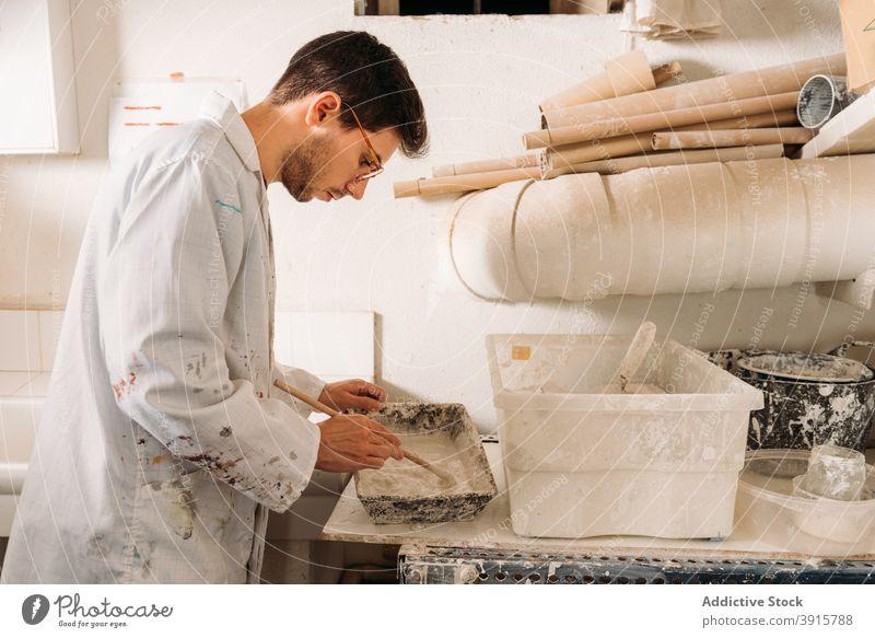 Handwerker bei der Arbeit mit Gips im Kunstatelier Kunstgewerbler verputzen Werkstatt Kunsthandwerker Form eingießen liquide Handarbeit Fähigkeit Mann männlich