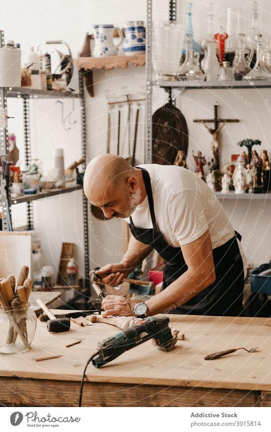 Kunsthandwerker bei der Herstellung von Holzdetails in der Werkstatt Zimmerer Holzarbeiten Beitel Hammer Arbeit kreieren schnitzen Instrument professionell