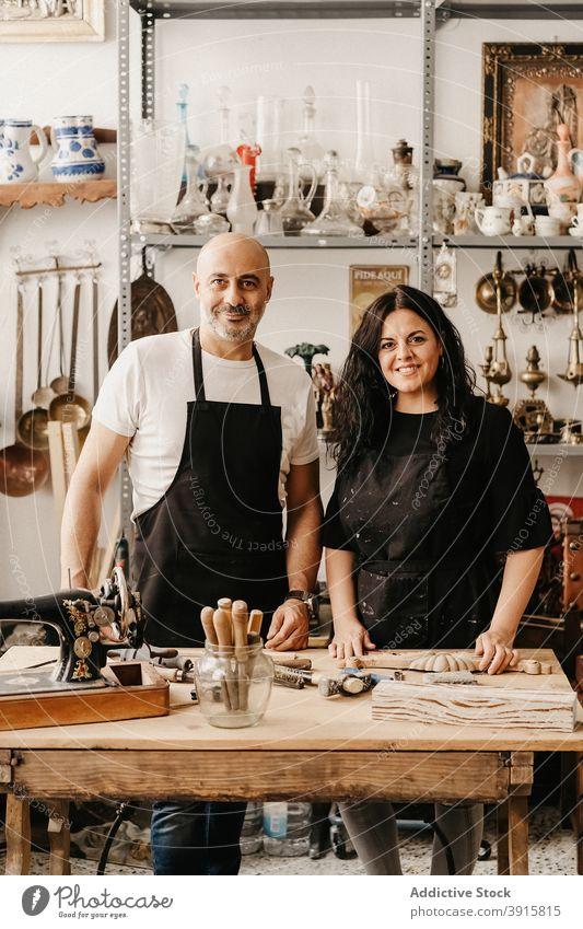 Fröhliches Kunsthandwerkerpaar an der Werkbank im Kunstatelier stehend Kunstgewerbler Paar Zimmerer Handwerk Zusammensein Werkstatt Arbeit Lächeln professionell