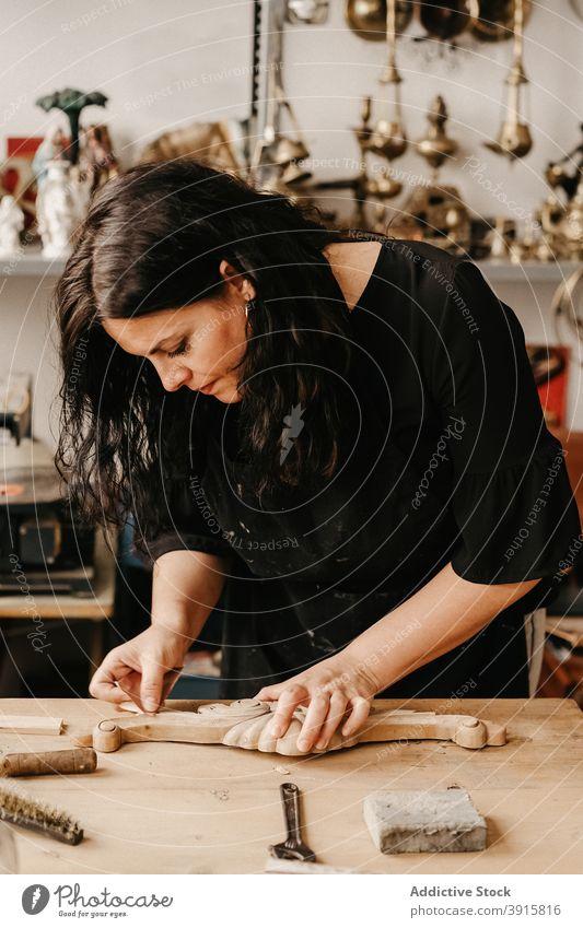 Handwerkerin poliert Holzdetail in der Werkstatt Zimmerer Holzarbeiten polnisch schnitzen Arbeit kreieren professionell hölzern Arbeitsplatz Tischlerin Frau