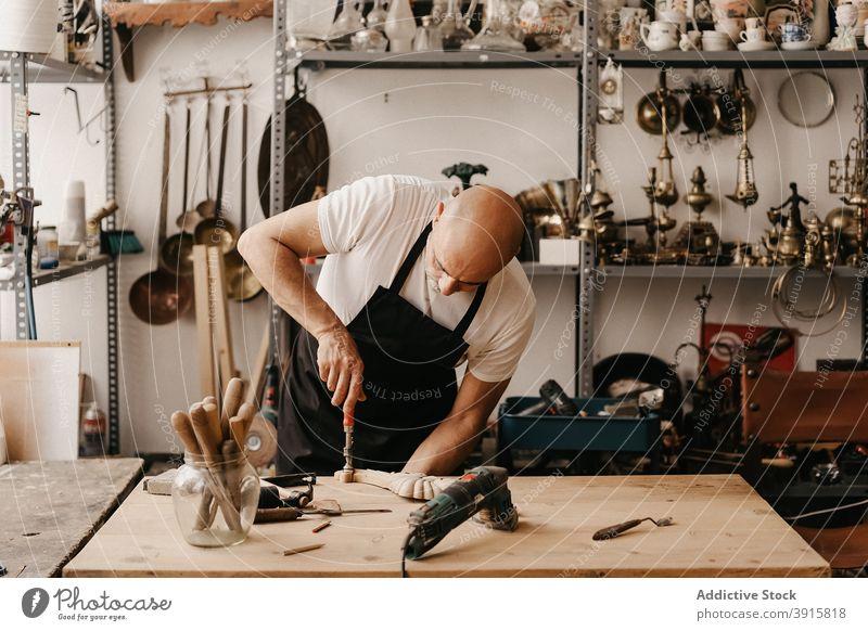 Handwerker schnitzt Holz in der Werkstatt Zimmerer schnitzen Holzarbeiten Beitel Hammer Arbeit kreieren Instrument professionell Werkzeug hölzern Arbeitsplatz
