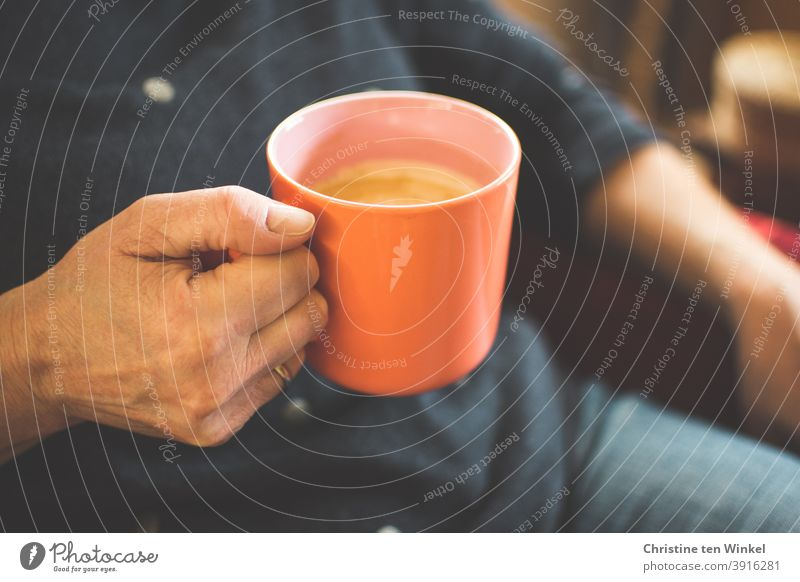 Entspannt im Sessel sitzen, eine Tasse Kaffee in der Hand... So kann das Wochenende beginnen ... Kaffeebecher festhalten Heißgetränk Becher Cappuccino wärmend