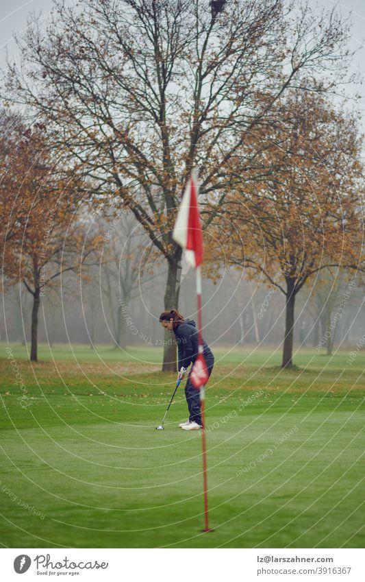 Fitte Golferin mittleren Alters beim Einlochen auf dem Grün von der Fahne aus gesehen, konzentriert auf den nächsten Schlag Frau Winter Herbst windig neblig
