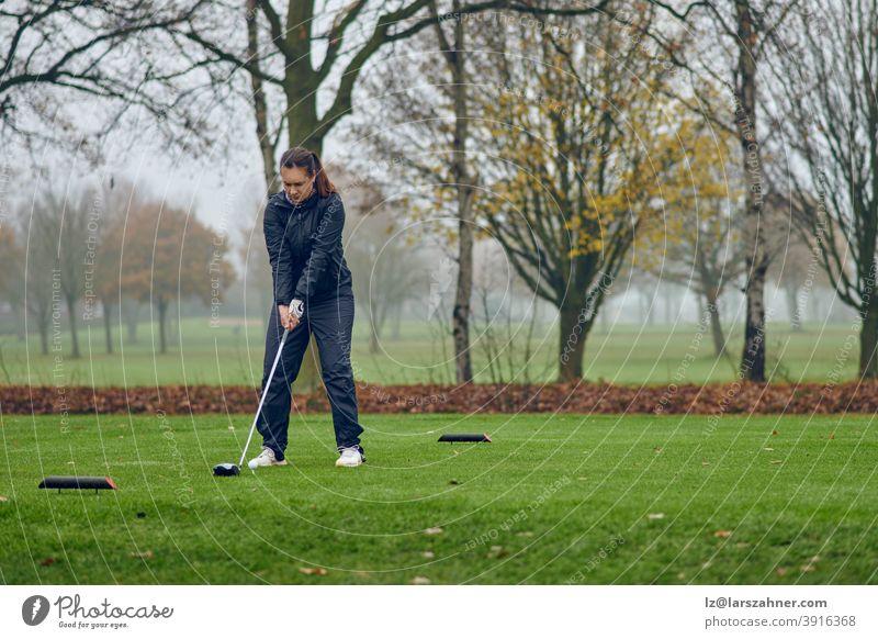 Frau mittleren Alters, die an einem kalten, nebligen Wintertag auf einem Parkland-Kurs Golf spielt und ihren Abschlag ausrichtet abschlagend Fahrer aufstellend