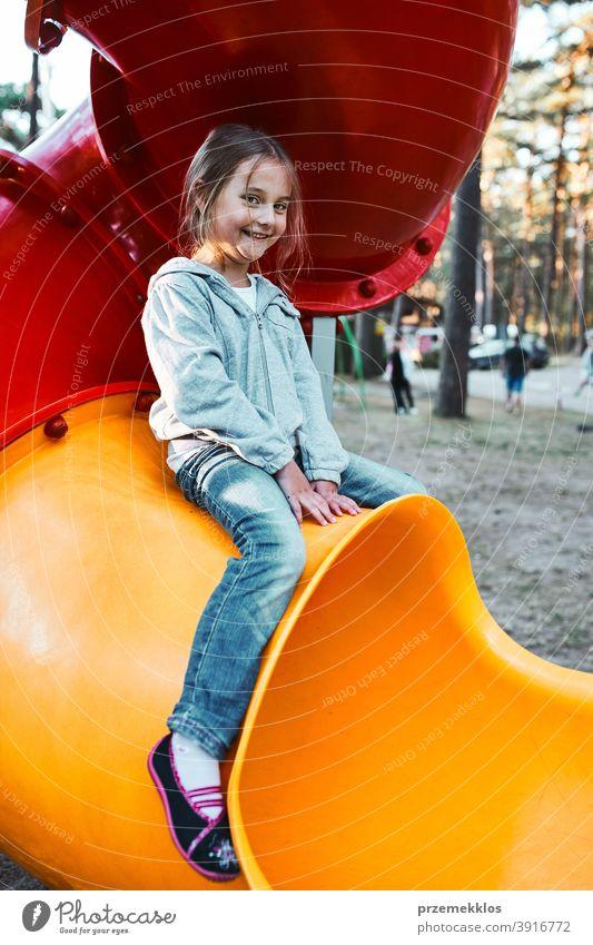 Kleines Mädchen Vorschüler spielen auf einem Spielplatz sitzen auf Rohr Rutsche lächelnd und Blick auf die Kamera positiv freudig Junior Öffentlich Ort
