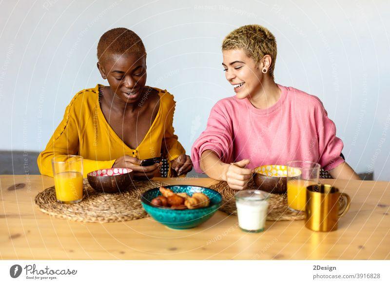 Zwei junge Frauen Paar, beste Freunde sitzen im Café, Frühstück essen und Kaffee trinken, mit Smartphone. Freundschaft häusliches Leben Zusammensein Lächeln