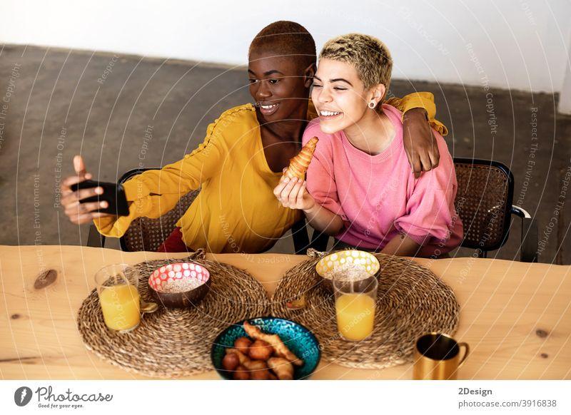 Schöne junge beste Freundin Frauen nehmen selfie mit einem Smartphone und lächelnd, während mit einem Frühstück zu Hause Selfie Freundschaft häusliches Leben