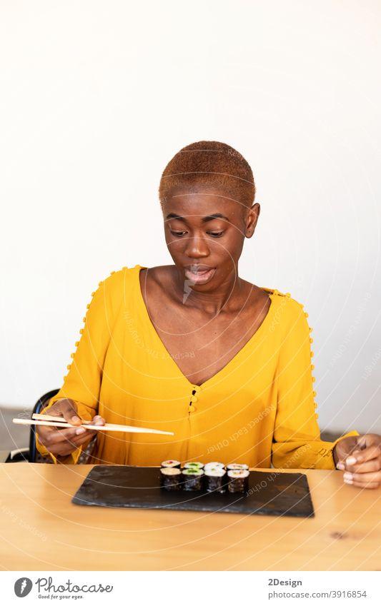 Afroamerikanische Frau essen Sushi mit Stäbchen zu Hause mit einem zuversichtlichen Ausdruck auf intelligente Gesicht denken ernst Afrikanisch Amerikaner