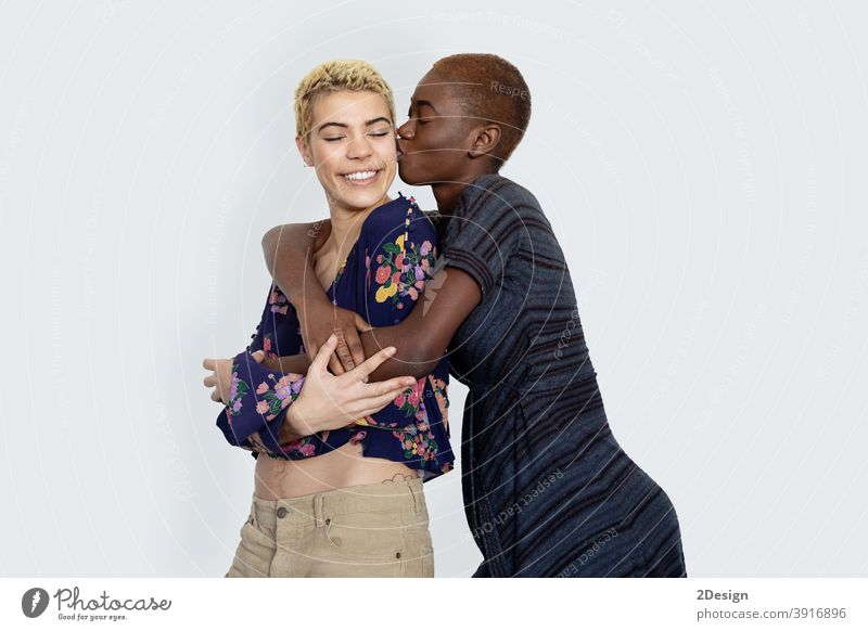 Foto von freudigen Damen küssen und umarmen Zweisamkeit, wobei von verschiedenen der Rassen, in lässigen Pullover gekleidet, isoliert über weißem Hintergrund.