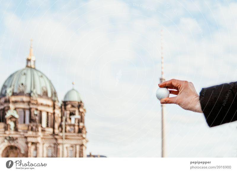 Golfball vor Berliner Fernsehturm gehalten Berlin-Mitte Wahrzeichen Alexanderplatz Himmel Berliner Dom Sehenswürdigkeit Hauptstadt Stadtzentrum Architektur Turm