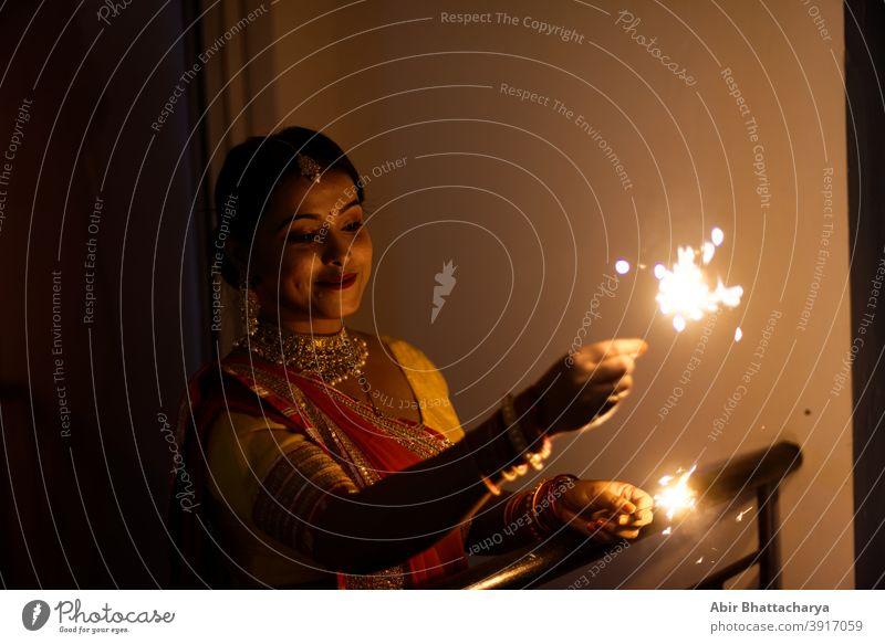 Junge und schöne indische Bengali Frau in indischen traditionellen Kleid feiert Diwali mit Feuer Cracker auf einem Balkon in der Dunkelheit. Indischer Lebensstil und Diwali-Feier