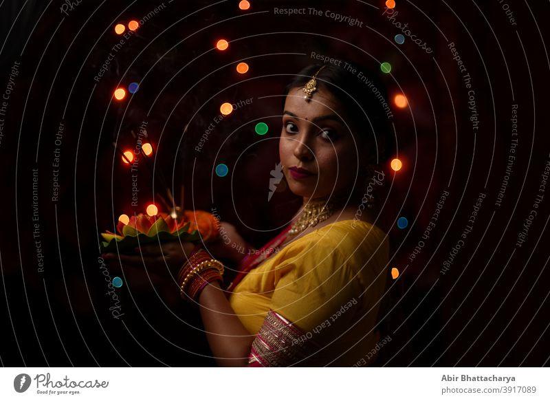 Eine junge und schöne indisch-bengalische Frau in indischer Tracht hält vor bunten Bokehlichtern eine Diwali diya/Lampe in der Hand. Indischer Lebensstil und Diwali-Feier