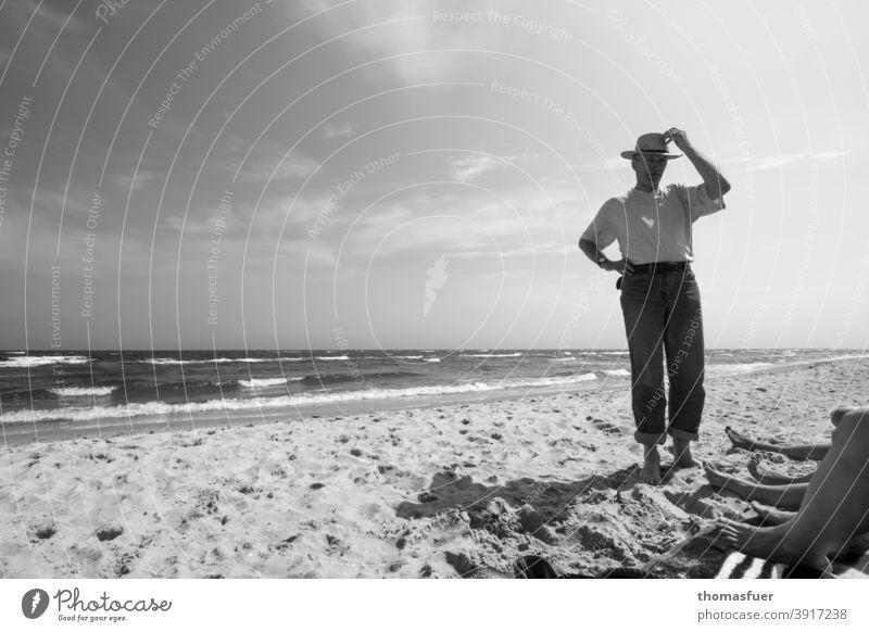 Mann mit Hut am Strand und Füße von einigen Damen bekleidet Hose T-Shirt Meer Wellen Bein Wind Sonne Wolken Schatten Sommerfrische Weite Urlaub Kontakt