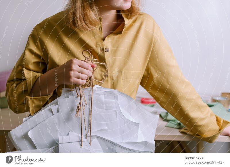 Frau in gelbem Hemd hält Papierkleidmuster in ihrer Werkstatt Schneider Handwerk Damenschneiderin Mode Muster Kleid Kleidungsmuster Bekleidung Beruf