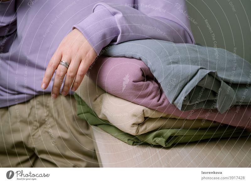 Frauenhand auf Stapel von pastellfarbenem Stoff Stoffe Baumwolle Textil Pastell Material Damenschneiderin gesichtslos Nahaufnahme verschiedene Haufen Mode