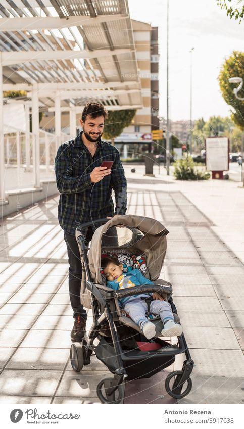 Bärtiger Mann mit seinem schlafenden Baby auf Auto schauen Telefon Vater Spaziergang Kleinwagen Männer männlich 40s Erwachsener attraktiv Herbst Vollbart bärtig