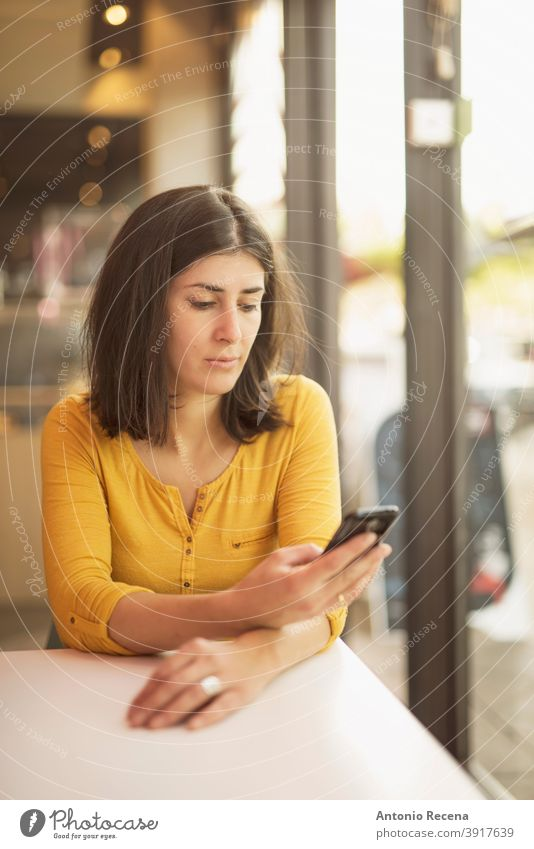 Frau in Bar in der Nähe von Fenster suchen Smartphone Telefon Blick hübsch Restaurant 30s ernst lesen Frauen Hinweise im Innenbereich Gelassenheit Nachrichten